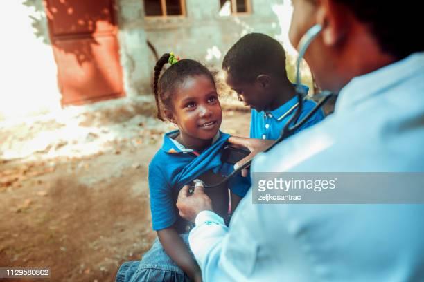 arzt treffen afrikanischen kindes - afrika stock-fotos und bilder