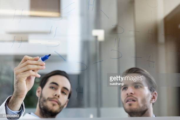 Doctor meeting with consultant, writing on glass whiteboard