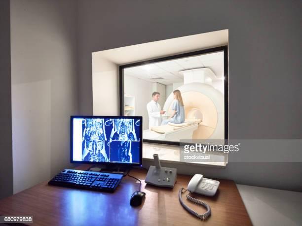 Doctor monitoring CAT scan procedure