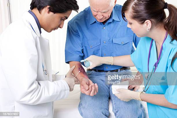 doctor, nurse treating man's wound, burn.  emergency room hospital. - wounded stock photos and pictures