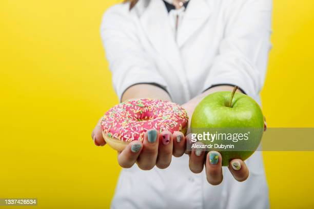 doctor nutritionist holding a sugar donut and a green apple on a yellow background. the concept of diet comparison. free place - natuurlijke staat stockfoto's en -beelden