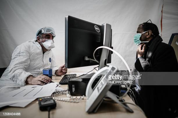 Doctor of a medical center testing patient for the COVID-19 virus talks with a man with a protective mask in Paris on March 27, 2020 during a strict...