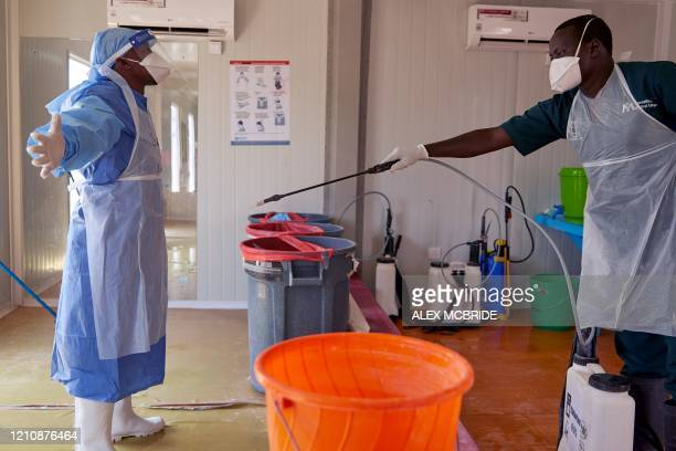 Doctor of International Medical Corps is disinfected at the isolation ward of Ministry of Health Infectious Disease Unit in Juba, South Sudan, on...