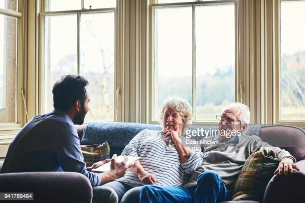 doctor on home visit discussing health of senior people - visit stock pictures, royalty-free photos & images
