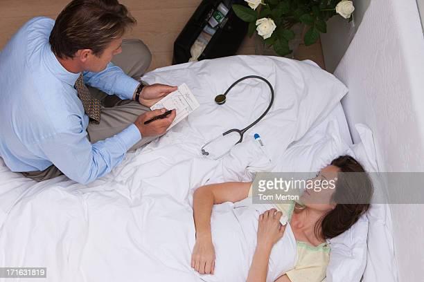Arzt auf Hausbesuch Schreiben verschreibungspflichtige für Kranke Frau