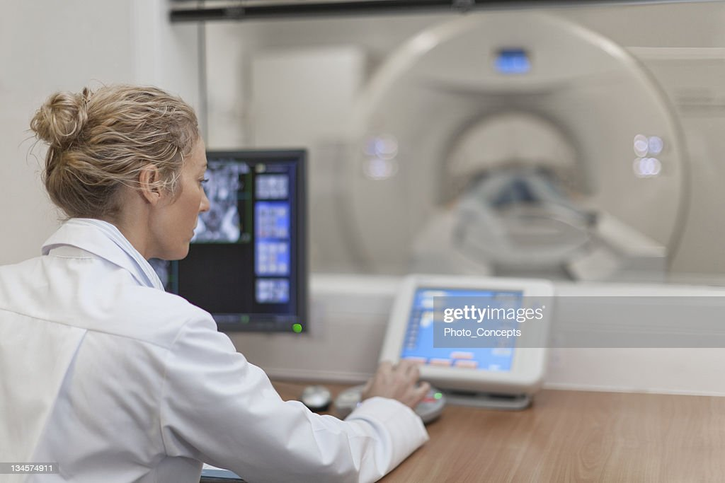 Doctor operating CT scanner in hospital : Stock Photo
