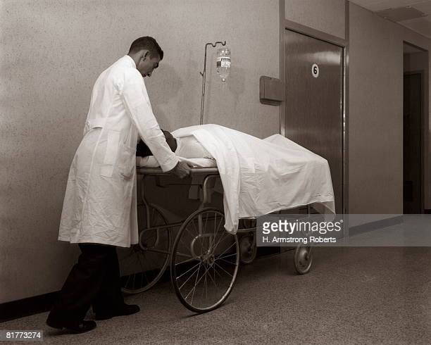 doctor orderly pushes patient lying on gurney stretcher hospital corridor charity hospital new orleans 1960s. - 20th century stock photos and pictures