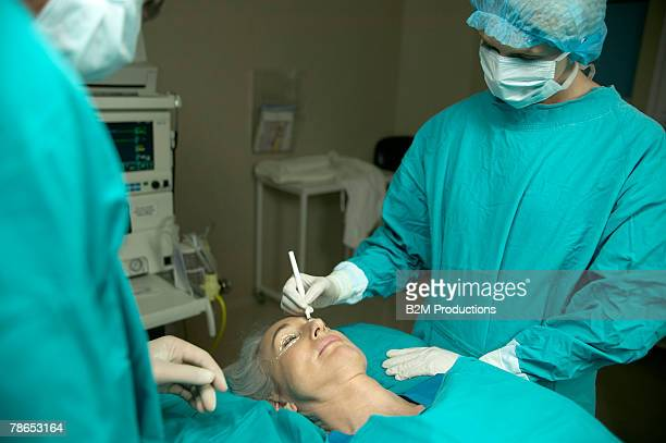 Doctor painting lines on woman's eyelid for surgery