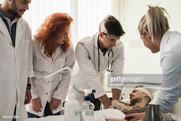 Doctor performing external heart massage on a patient at clinic.