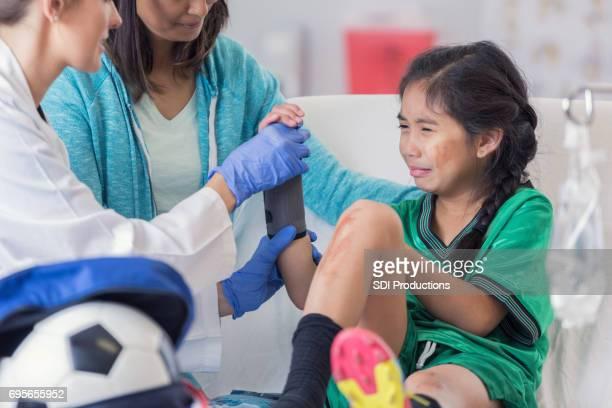 Notarzt legt Handgelenkbandage auf Arm des jungen Patienten