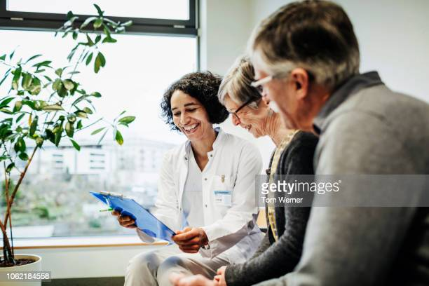 doctor pleased with elderly couple's test results - doctor and patient stock pictures, royalty-free photos & images