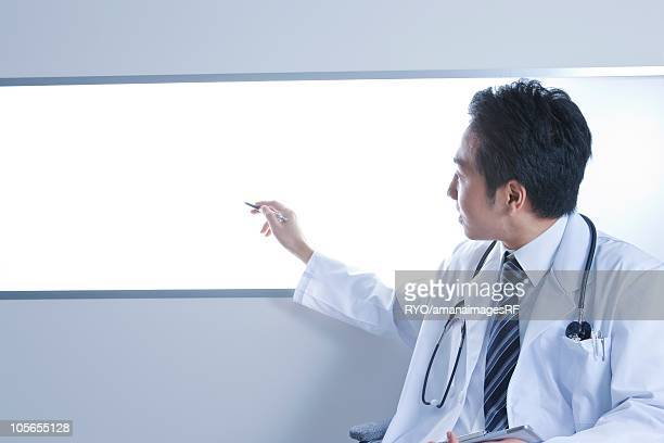 Doctor pointing lightbox with a pen