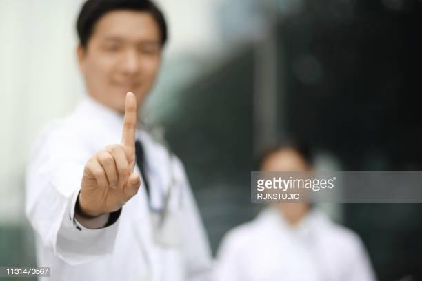doctor pointing up finger - première photos et images de collection