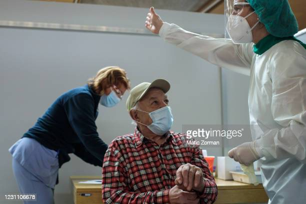 Doctor points to the direction of the exit after vaccinating an elderly person on February 11, 2021 in Kranj, Slovenia. Slovenia plans to vaccinate...