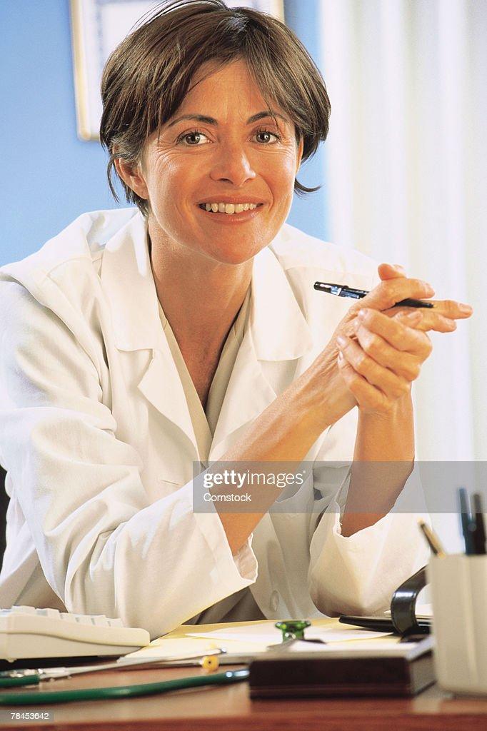 Doctor posing at her desk : Stockfoto