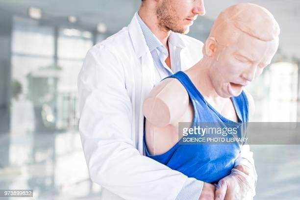 doctor practising heimlich manoeuvre - 喉が詰まる ストックフォトと画像