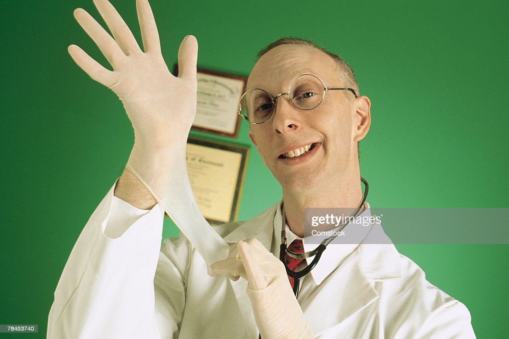 Doctor pulling on gloves : Stockfoto