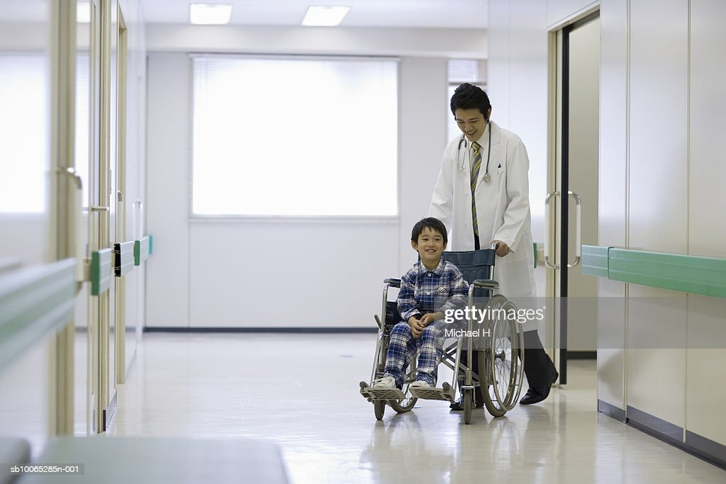 Doctor pushing boy (5-6) in wheelchair in hospital corridor : Foto stock