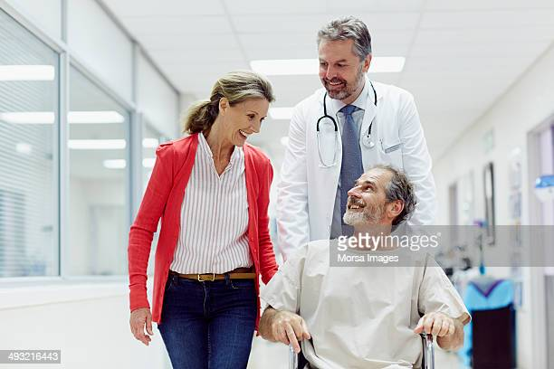 Doctor pushing male patient in wheelchair