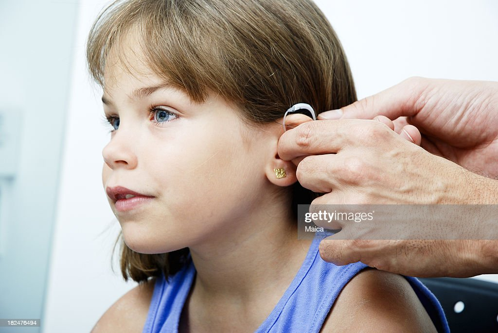 Doctor putting an earhorn in a child's ear : Stockfoto