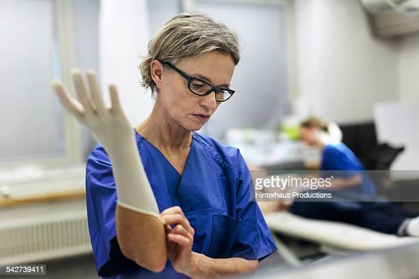doctor putting on gloves - schutz und arbeitskleidung stock-fotos und bilder