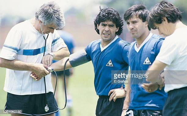 Doctor Raul Madero checks Diego Maradona of Argentina as he talks to teammate Julio Olarticoechea during a training session ahead of the 1986 FIFA...