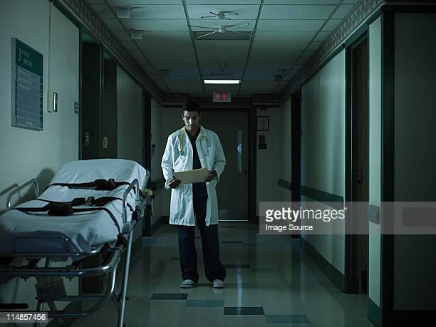 Médecin lisant Tableau médical à l'hôpital corridor