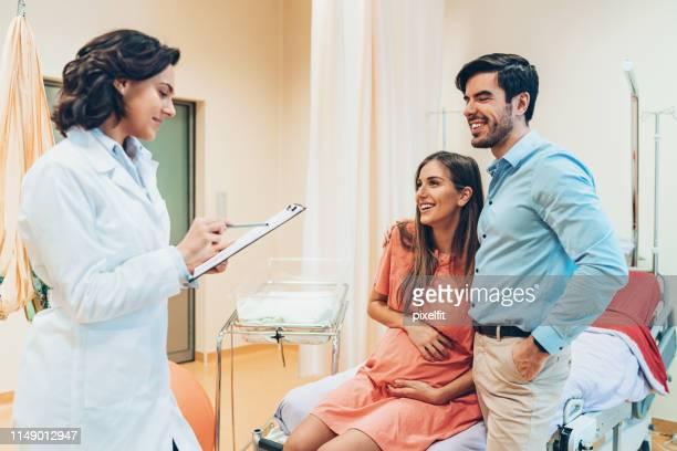 doctor leyendo la grabación de una mujer embarazada - cesarea fotografías e imágenes de stock