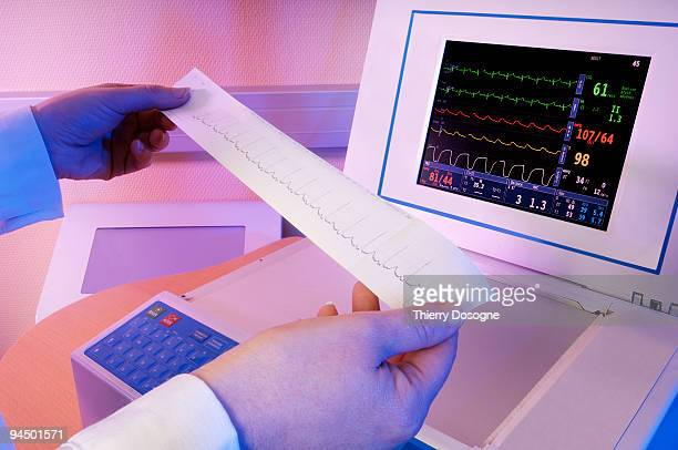 doctor reading the electrocardiogram graphic - cardiologist stock pictures, royalty-free photos & images