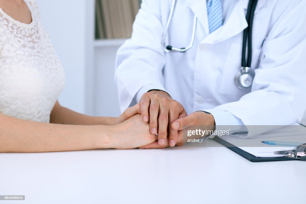 Doctor Reassuring His Female Patient By Touching Her Hands While