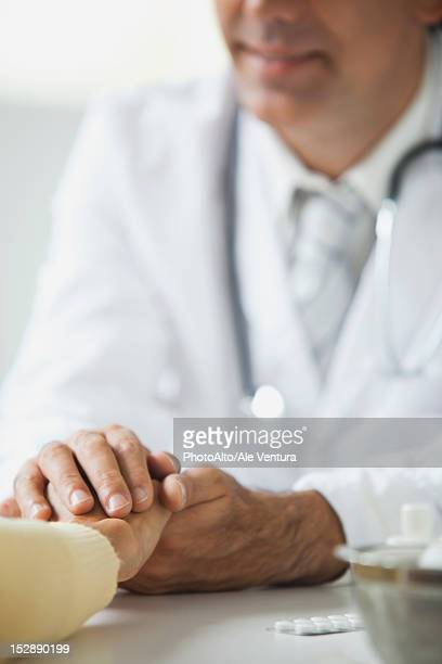 Doctor reassuring patient during consultation, cropped