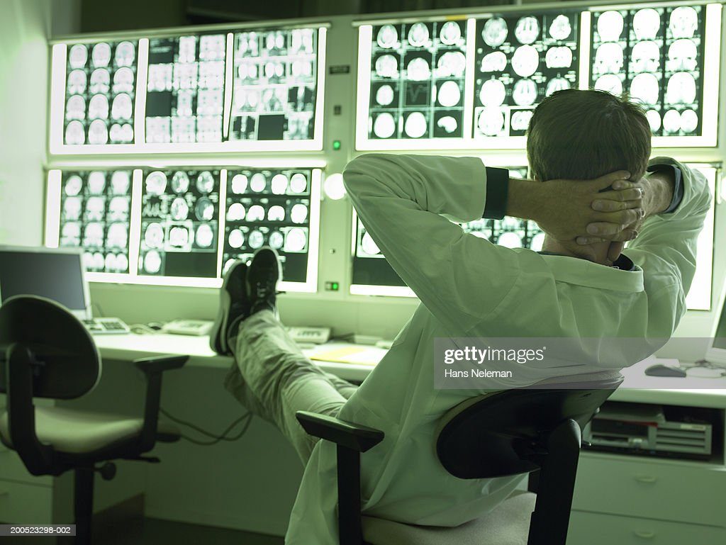 Doctor relaxing with feet up in x-ray laboratory : Stockfoto