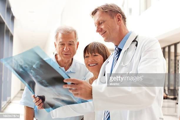 Doctor reviewing an x-ray image with patients