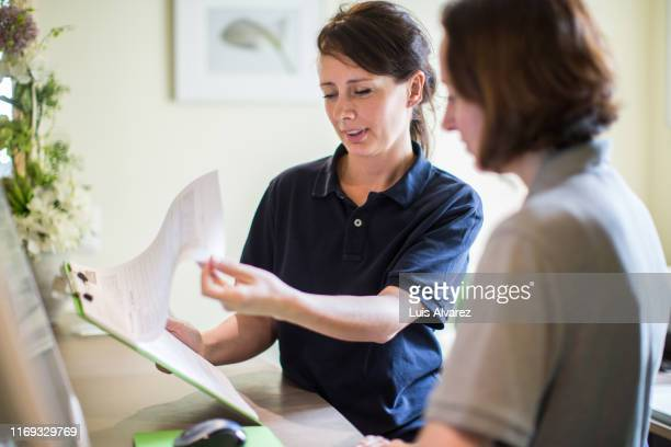 doctor reviewing at patient appointment list - medical receptionist uniforms - fotografias e filmes do acervo