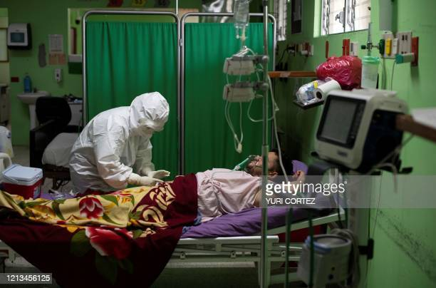 A doctor reviews a patient infected with the novel coronavirus COVID19 while he remains connected to artificial respiration devices and receives...