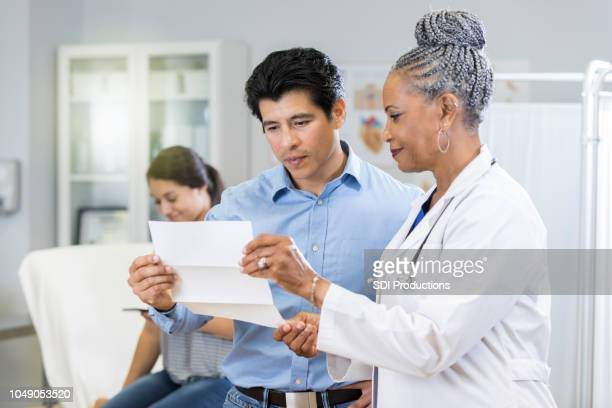 doctor reviews test results with concerned father - financial bill stock pictures, royalty-free photos & images
