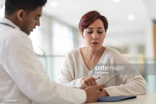doctor reviews test results with female patient - hearing protection stock pictures, royalty-free photos & images