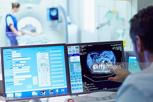 doctor running ct scan from control room - science and technology stock pictures, royalty-free photos & images