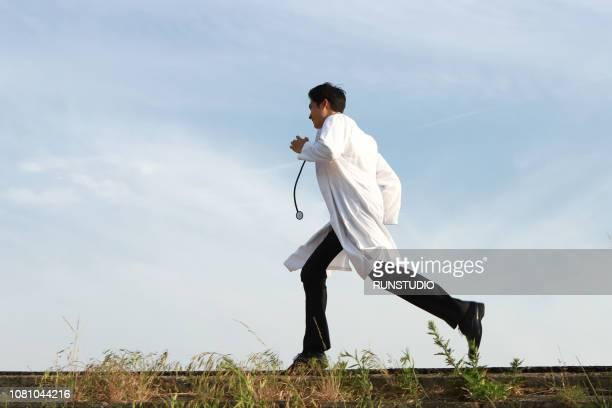 doctor running, side view - 白衣 ストックフォトと画像