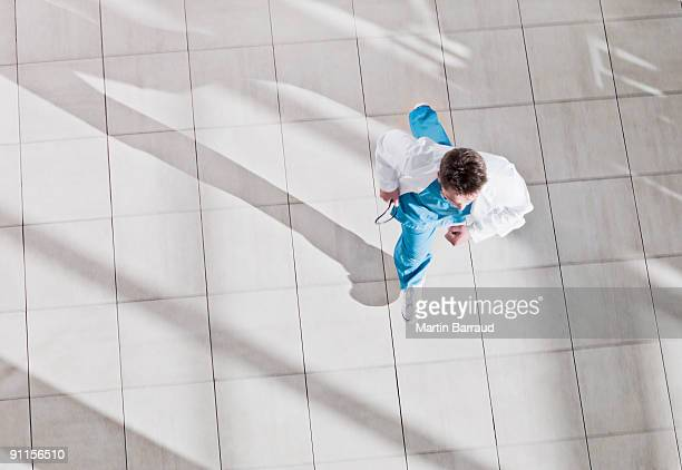 doctor running through hospital lobby - dringendheid stockfoto's en -beelden
