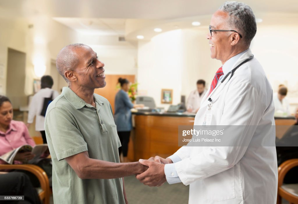 Doctor shaking hand of patient in hospital : Foto stock