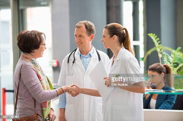 doctor shaking hands with his patient at hospital reception desk - medical receptionist uniforms - fotografias e filmes do acervo