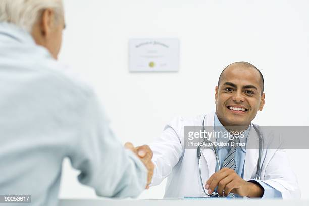 Doctor shaking hands with patient, smiling at camera, cropped