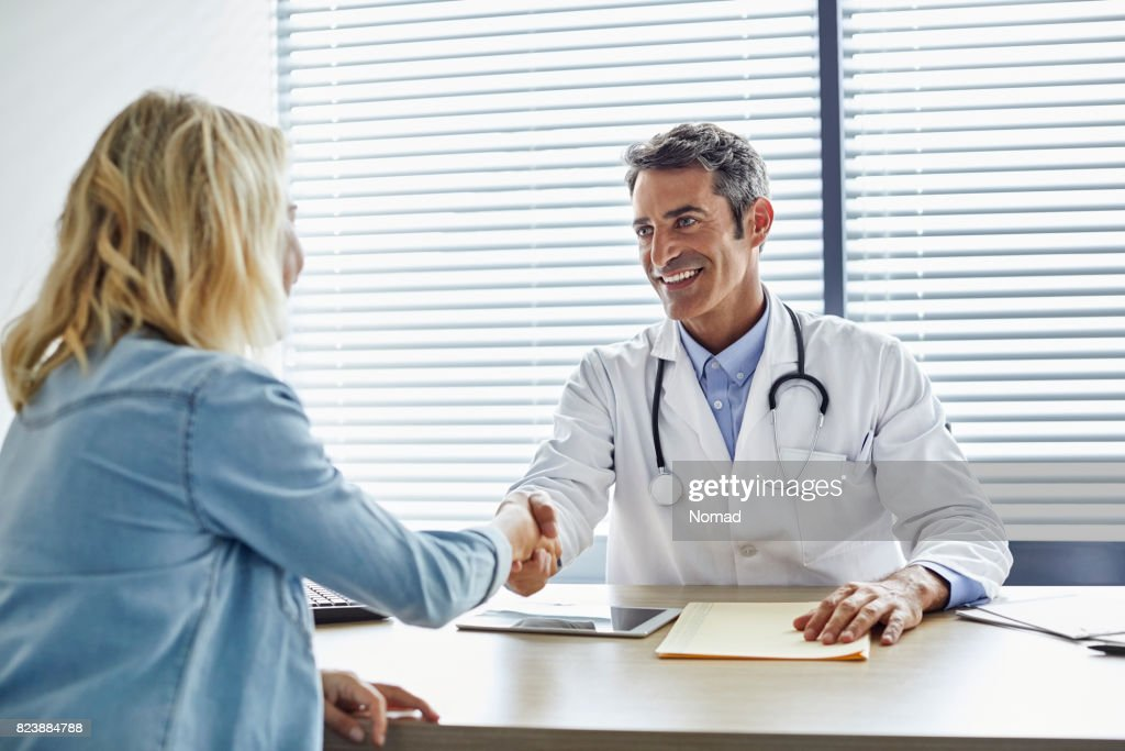 Doctor shaking hands with woman at hospital : Stock Photo