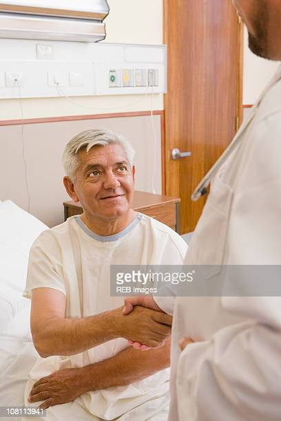 Doctor shaking patient's hand in hospital room