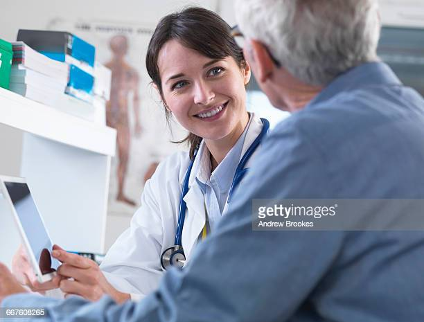 Doctor sharing health information on digital tablet with patient in clinic