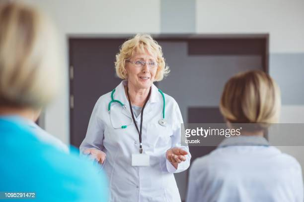 doctor sharing her experience with young medical staff - izusek stock pictures, royalty-free photos & images