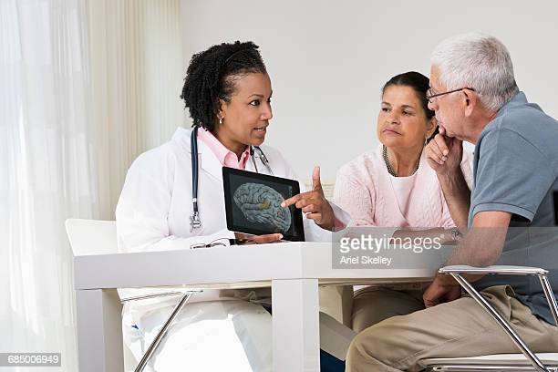 Doctor showing brain x-ray on digital tablet to patients