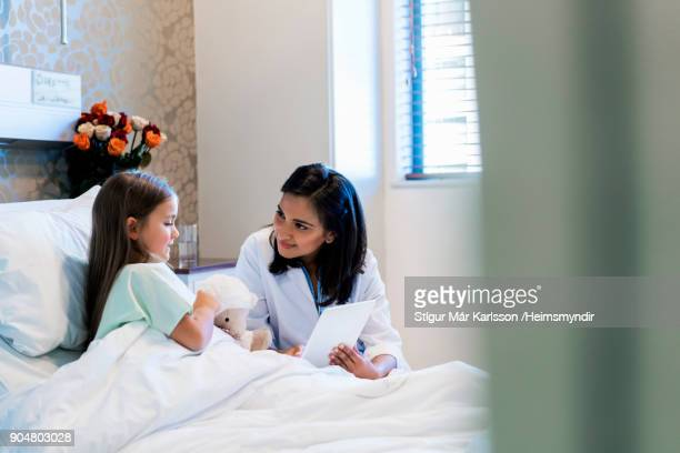 doctor showing digital tablet to patient - girl in hospital bed sick stock photos and pictures