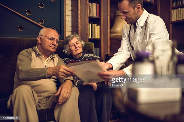 Doctor showing medical documents to a senior couple at home.